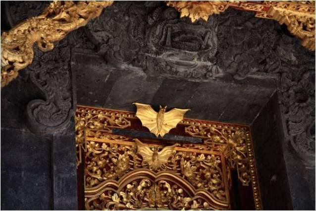 Среди множества религиозных мест на Бали есть пещерный храм Гоа Лавах, в котором живет множество летучих мышей. Это одна из девяти самых важных святынь, защищающих территорию острова от злых духов. Путешественники и балийцы посещают святилище для духовного очищения, а также ради уникальной возможности посмотреть на множество летучих мышей и ритуальные церемонии. Что собой представляет храм? Гоа Лавах (Pura Goa Lawah) – это действующий индуистский храм, находящийся в небольшой балийской деревне Песинггахан, регентства Клунгкунг. Храм входит в число Sad Kahyangan Jagad или «шесть святынь мира», и является одним из шести балийских национальных храмов, призванных обеспечить духовное равновесие. Храм Гоа Лавах построен на холмистой местности, вокруг пещеры, являющейся домом для летучих мышей. Отсюда произошло название святыни Goa Lawah, что переводится с балийского языка как «пещера летучих мышей» (Goa – «пещера», Lawah – «летучая мышь»). Храмовая территория разделена на 3 зоны: внешний, средний, внутренний двор. Тихий внешний двор с небольшим садом ведет к среднему двору, богато украшенному резными черными воротами из камня и лавы. Пещера летучих мышей Во внутреннем дворе находится главная достопримечательность храмового комплекса – природная пещера, населенная летучими мышами. Согласно легенде, она ведет к главному балийскому храму Бесаких 20-километровым подземным туннелем. По преданию в темных углублениях туннеля живет мифический гигантский змей Нага Басуки. Считается, что эта древняя рептилия является хранителем земного равновесия. Это убеждение происходит от доиндуистского анимизма. Местные жители также верят, что под пещерой протекает река целебных вод. В древних храмовых сооружениях, расположенных в устье пещеры, ежедневно совершается паломничество при виде бесчисленных сонных кожанов, висящих вверх ногами вокруг входа. Местные жители считают летучих мышей священными существами и почитают их. Животные расположены так близко друг к другу, что поверхность пещеры на